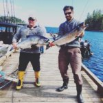Two men showing off their chinook salmon