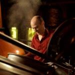 Distiller Checking Whiskey in Still