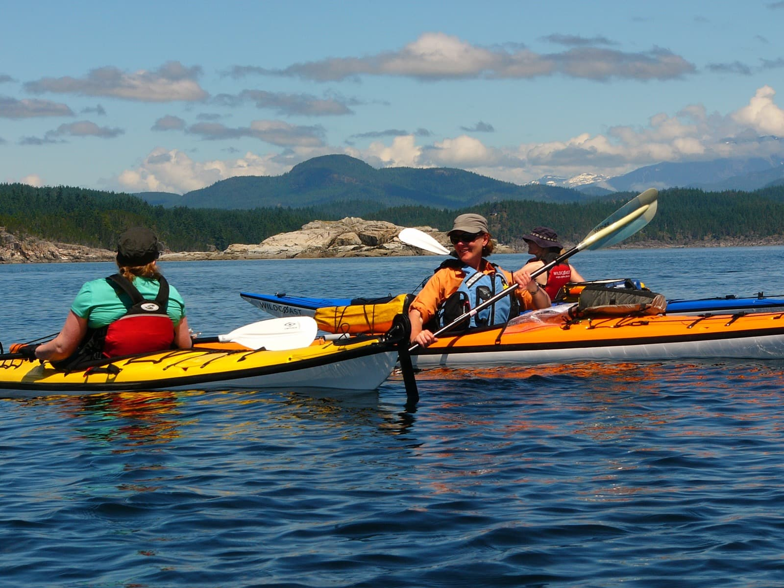 Three kayakers talking to each other in calm water